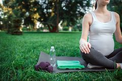 Cut view of young pregnant woman sit in lotus pose on yoga mate in room. She has water bottle, dumbbells and green towel stock image