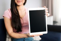Cut view of young woman sit on sofa. She hold white tablet in hands and show it black screen to camera. Model smiles. royalty free stock image