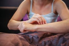 Cut view of young woman sitting on bed and touching her skin with one hand. She is in room alone. Her legs are covered. With blanket. Woman has problem royalty free stock photos