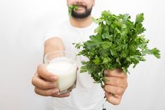Cut vuew of bearded young man holding glass of kefir and bunch of parsley in hands. He shows it to camera. Also young stock photos