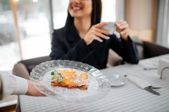 Cut vuew of cheerful young customer smiles. She hold cup of hot drink and look at waitress. Female worker has plate with royalty free stock photos