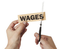 A cut in wages. Hand with scissors cutting into a label signed wages Stock Image
