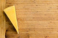 Cut wedge of fresh Dutch Maasdam cheese. With its yellow rind as a side boarder on an old bamboo cheese board with copy space viewed from overhead royalty free stock images