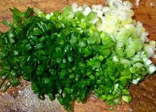 Cut wet green onion. On a wood desk in the kitchen. Very useful in spring salads royalty free stock images
