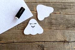 Cut from white felt details for sewing Halloween ghost. On one side embroidered with black thread eyes and mouth. Step Stock Images