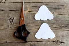 Cut white felt details to make Halloween ghost ornament. Scissors on old wooden background. Halloween kids crafts. Step. Sewing technique for kids. Top view royalty free stock image