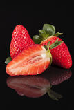 Cut and whole fresh fruits of red strawberry isolated on black background Royalty Free Stock Images