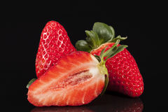 Cut and whole fresh fruits of red strawberry isolated on black background Royalty Free Stock Photo