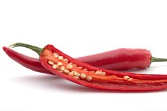Cut and whole pepper. A cut red chili pepper, with seeds visible, a whole pepper behind it, isolated on white Stock Photo