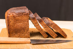 Cut wholemeal bread and knife Stock Image