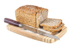 Cut wholemeal bread and knife on a chopping board Royalty Free Stock Photos