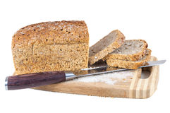 Cut wholemeal bread and knife on a chopping board Stock Images