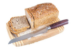 Cut wholemeal bread and knife on a chopping board Stock Image