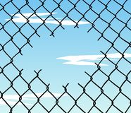 Cut wire fence with blue sky background Royalty Free Stock Photo