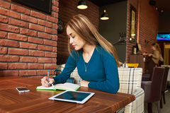 Cut woman lawyer is using digital table,. Woman entrepreneur doing monthly report on net-book while sitting in modern interior cafe. smart female bookkeeper Stock Photo