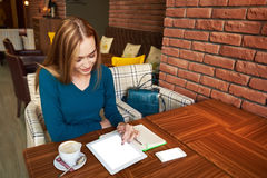 Cut woman lawyer is using digital table,. Experienced female freelancer create new design of website on digital tablet  while sitting in modern interior Royalty Free Stock Photos