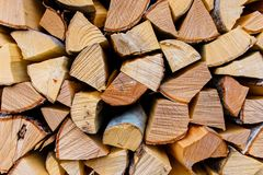 Cut wooden logs stacked along wall. Textured background stock photography