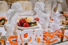 Сut word love with white angels and candles on the festive table for newlyweds. Stock Image
