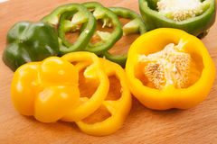 Cut yellow and green bell peppers on cutting board Royalty Free Stock Photos