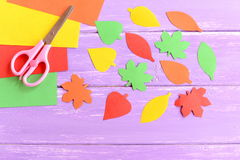 Cut yellow, green, red and orange paper leaves, scissors, colored paper sheets on lilac wooden background. Closeup Royalty Free Stock Photos