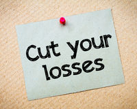 Cut your losses. Message. Recycled paper note pinned on cork board. Concept Image stock images