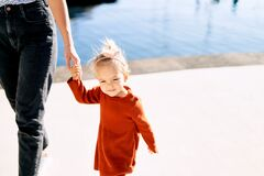 Free Cute 2-year Old Girl Is Holding Her Mother`s Hand During A Walk By The Sea Stock Photos - 202354483