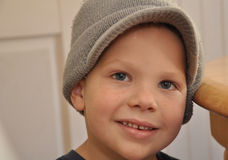 Cute 5 Year Old Boy Smiling. This closeup facial photo is a cute 5 year old Caucasian boy with freckles wearing a gray hat Stock Photography
