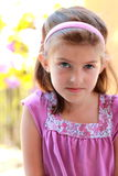 A cute 8 year old girl in pink. A cute little 8 year old girl in a pink blouse with brown hair. Shallow depth of field Royalty Free Stock Photography