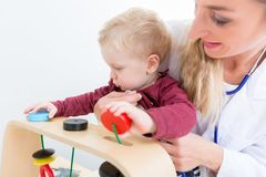 Cute active baby boy playing with toys during physical examination royalty free stock image