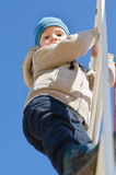 Cute active child climbing up a ladder in the park. Outdoor, under a clear blue sky, shot from low angle Stock Image