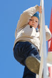 Cute active child climbing up a ladder in the park. Outdoor, under a clear blue sky, shot from low angle Royalty Free Stock Photography