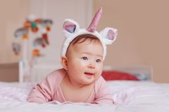 Free Cute Adorable Asian Mixed Race Smiling Baby Girl Four Months Old Lying On Tummy On Bed In Bedroom Wearing Unicorn Headband Horn A Royalty Free Stock Images - 148977789