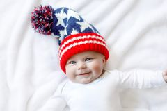 Cute adorable baby child with Christmas winter cap on white background. Happy baby girl or boy smiling and looking at the camera. Close-up for xmas holiday and Stock Images