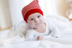 Cute adorable baby child with Christmas winter cap on white background. Happy baby girl or boy smiling and looking at royalty free stock image