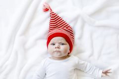 Cute adorable baby child with Christmas winter cap on white background. Happy baby girl or boy smiling and looking at. The camera. Close-up for xmas holiday and stock photos