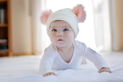 Cute adorable baby child with warm white and pink hat with cute bobbles Stock Photos