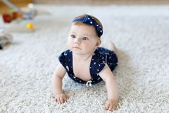Cute adorable baby girl in blue clothes and headband. little child looking at the camera and crawling. Baby learning. Grab on white background. Portrait of royalty free stock photography