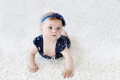 Cute adorable baby girl in blue clothes and headband. little child looking at the camera and crawling. Baby learning. Grab on white background. Portrait of royalty free stock images