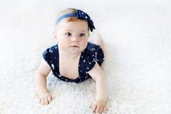 Cute adorable baby girl in blue clothes and headband. Stock Photos