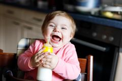 Cute adorable ewborn baby girl holding nursing bottle and drinking formula milk. Cute adorable baby girl holding nursing bottle and drinking formula milk. First stock images