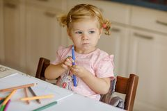 Cute adorable baby girl learning painting with pencils. Little toddler child drawing at home, using colorful felt tip. Pens. Healthy happy daughter royalty free stock photo