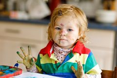 Cute adorable baby girl learning painting with water colors. Little toddler child drawing at home, using colorful royalty free stock photography