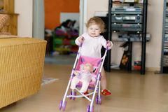 Cute adorable baby girl making first steps with doll carriage. Beautiful toddler child pushing stroller with toy at home. Happy daughter Royalty Free Stock Photography