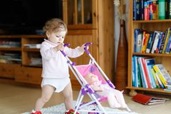 Cute adorable baby girl making first steps with doll carriage. Beautiful toddler child pushing stroller with toy at home. Happy daughter Stock Photography