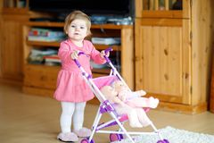 Cute adorable baby girl making first steps with doll carriage. Beautiful toddler child pushing stroller with toy at home. Happy daughter Stock Image