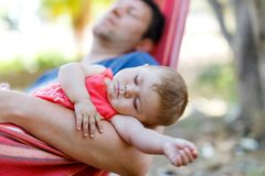 Cute adorable baby girl of 6 months and her father sleeping peaceful in hammock in outdoor garden. Closeup of beautiful child, little newborn kid sleeping Royalty Free Stock Photography