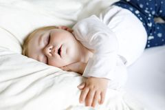 Cute adorable baby girl of 6 months sleeping peaceful in bed Stock Photos