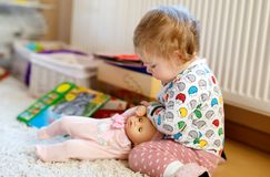 Cute adorable baby girl playing with first doll. Beautiful toddler child at home. Happy daughter Royalty Free Stock Photo