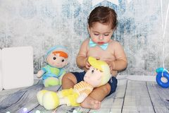 Cute adorable baby playing with dolls stock photos