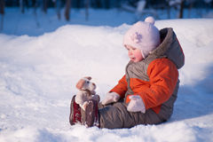 Cute adorable baby sit on snow. In winter park with small toy dog on legs Stock Photos